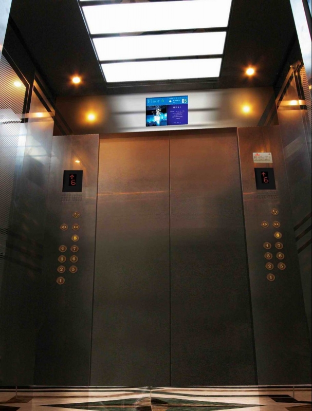 Inside an elevator car with lights and a display