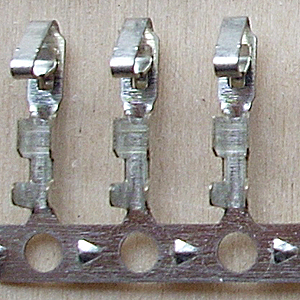 Несущая лента расположена внизу, и контакты прикреплены к ней перемычками. Контакты на такой ленте пригодны для использования как на автоматизированном оборудовании, так и с помощью ручного инструмента